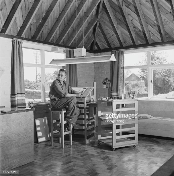British cartoonist Carl Giles at work in his studio on his farm in Suffolk, June 1948. Giles built the studio and much of its furniture himself. He...