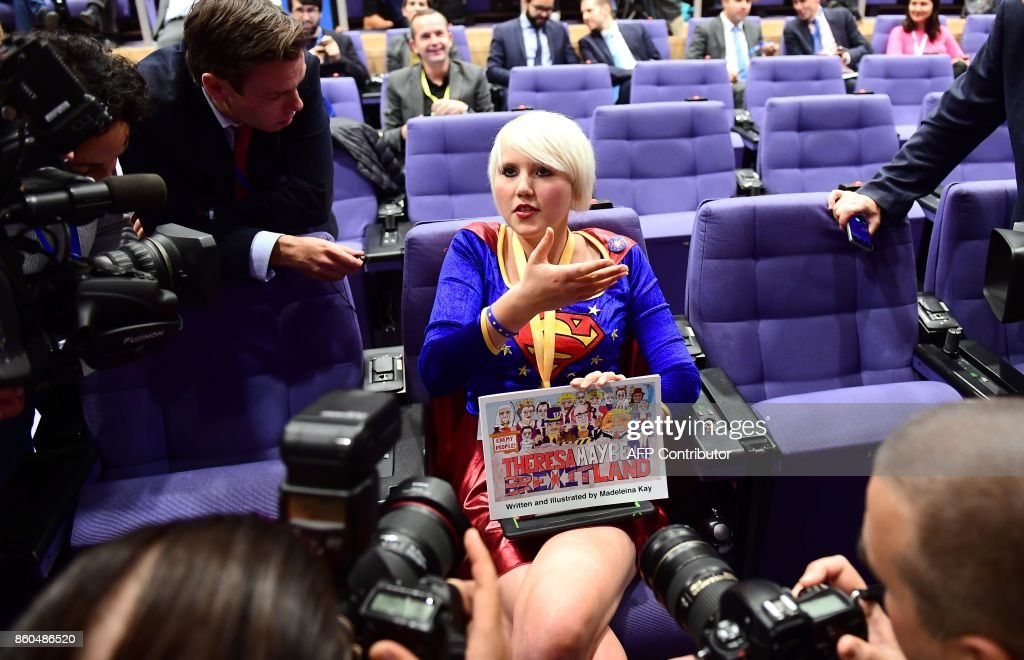 British cartoonist Madeleine Kay, an anti-Brexit activist wearing a costume of Superwoman, speaks to journalists as she tries to attend a press conference by British Secretary of State for Exiting the European Union (Brexit Minister) David Davis and European Union Chief Negotiator in charge of Brexit negotiations with Britain Michel Barnier at the European Union Commission in Brussels on October 12, 2017. /