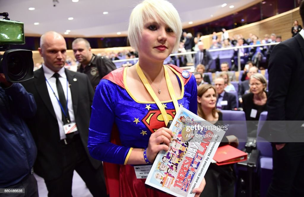 British cartoonist Madeleine Kay, an anti-Brexit activist wearing a costume of Superwoman, is escorted out prior to a press conference by British Secretary of State for Exiting the European Union (Brexit Minister) David Davis and European Union Chief Negotiator in charge of Brexit negotiations with Britain Michel Barnier at the European Union Commission in Brussels on October 12, 201 /