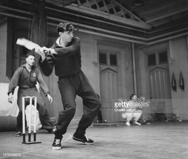 British champion steeplechaser John Disley swings a cricket bat with a wicket keeper and someone lifting a barbell in the background in the gymnasium...