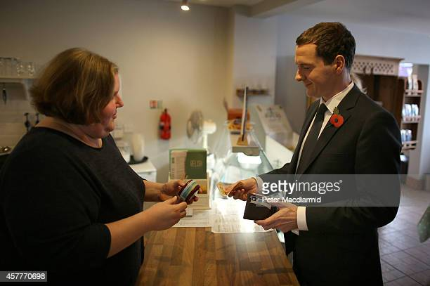 British Chancellor of the Exchequer George Osborne buys some cheese from Relsih cafe owner Emmas Corbett on October 24, 2014 in Beeston, England. The...