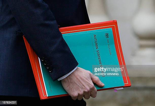 British Chancellor of the Exchequer George Osborne holds his Autumn budget as he leaves the Treasury to deliver his statement in the House of Commons...