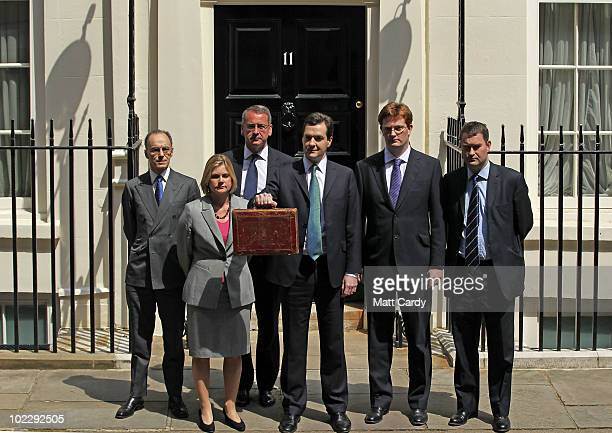 British Chancellor of the Exchequer George Osborne holds the budget box as he stands with his treasury team: Financial Secretary to the Treasury Mark...