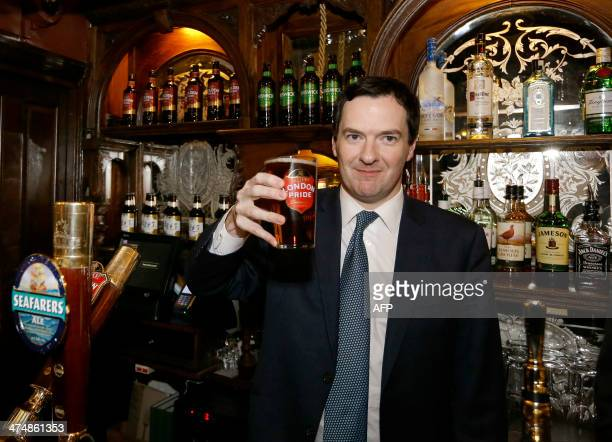 British Chancellor of the Exchequer George Osborne holds up a pint of beer during a visit to officially reopen The Red Lion pub following a major...