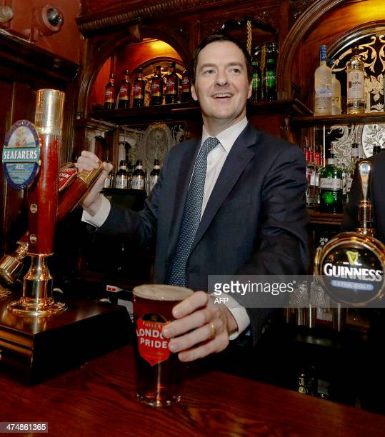 British Chancellor of the Exchequer George Osborne pulls a pint of beer during a visit to officially reopen The Red Lion pub following a major...