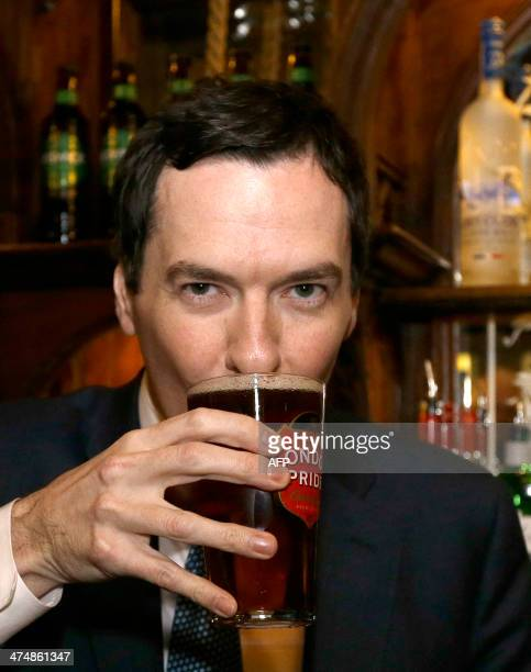 British Chancellor of the Exchequer George Osborne sips a pint of beer during a visit to officially reopen The Red Lion pub following a major...