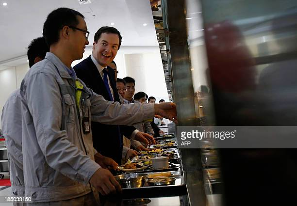 British Chancellor of the Exchequer George Osborne talks with workers as they collect food at a canteen near a nuclear reactor under construction at...