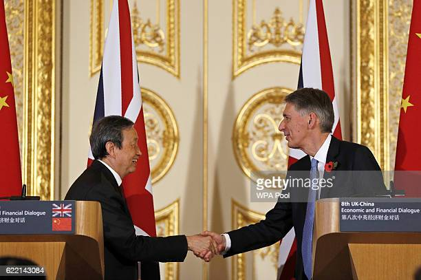 British Chancellor of the Exchequer Philip Hammond and Chinese Vice Premier Ma Kai host shake hands during a joint press conference where they...