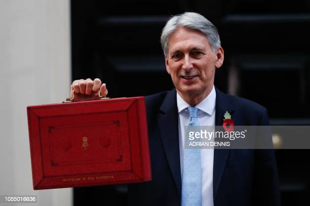 British Chancellor of the Exchequer Philip Hammond poses for pictures with the Budget Box as he leaves 11 Downing Street in London on October 29...