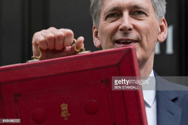 British Chancellor of the Exchequer Philip Hammond poses for pictures with the Budget Box as he leaves 11 Downing Street in London on March 8 before...