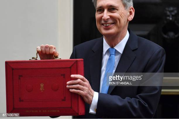 British Chancellor of the Exchequer Philip Hammond poses for pictures with the Budget Box as he leaves 11 Downing Street in London on November 22...