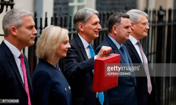 British Chancellor of the Exchequer Philip Hammond poses with the Budget Box as he stands with members of his ministerial team Britain's Chief...