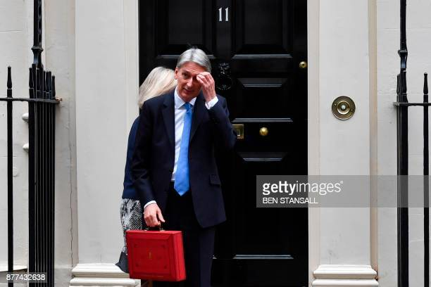 British Chancellor of the Exchequer Philip Hammond scratches his head as he waits for his ministerial team to depart before posing with the Budget...