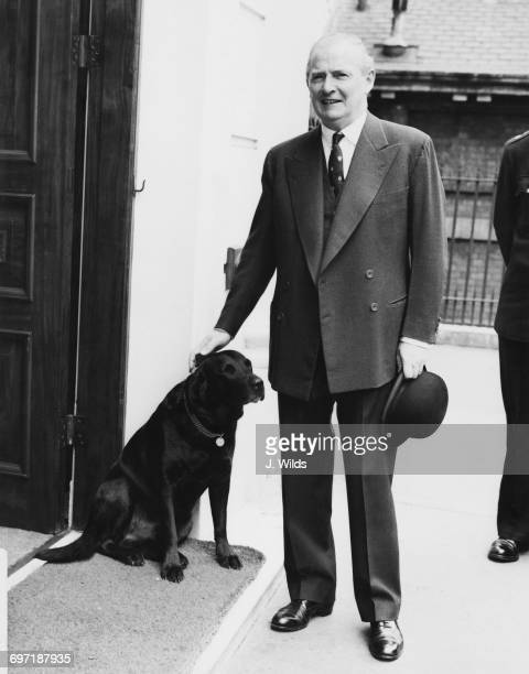 British Chancellor of the Exchequer Selwyn Lloyd pats his pet dog as he leaves at his official residence at Carlton Gardens on his way to the...