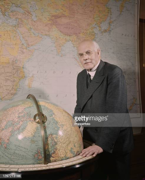 British chemist and businessman Harold Hartley , Chairman of the British Overseas Airways Corporation posed with a globe in front of a map of the...