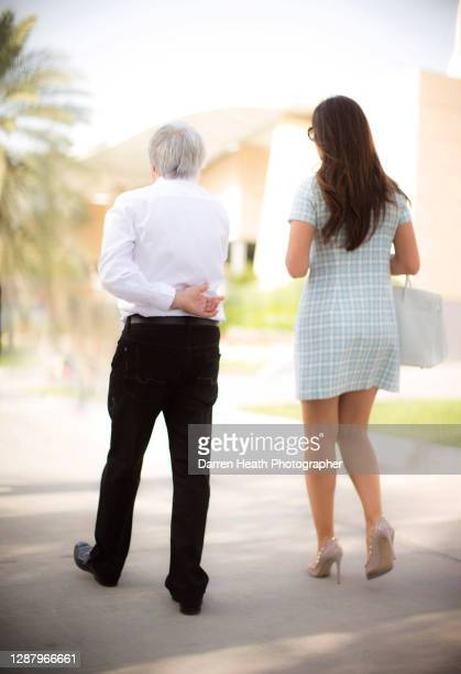 British Chief Executive of The Formula One Group Bernie Ecclestone with his Brazilian wife Fabiana Flosi walking in the F1 paddock at the 2017...