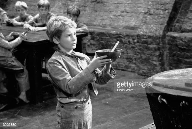 British child star Mark Lester as Oliver Twist asking for some more gruel during the filming of 'Oliver'