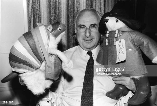 British children's book author Michael Bond stands with stuffed animal toys of his characters Paddington Bear and JD Polson the Armadillo June 27 1981