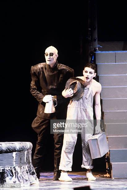 British choreographer, mime and actor Lindsay Kemp raising a suitcase in a play, wearing make-up and a stage costume. 1980s.