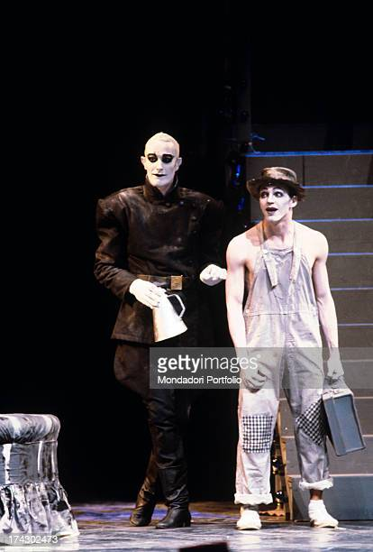 British choreographer mime and actor Lindsay Kemp raising a suitcase in a play wearing makeup and a stage costume 1980s