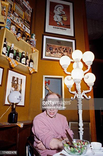 British choreographer mime and actor Lindsay Kemp sitting in a restaurant at a table laid with a salad smiling with his arms folded 1980s