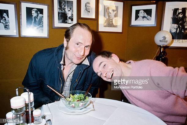 British choreographer, mime and actor Lindsay Kemp, sitting in a restaurant, smiling beside sociologist Francesco Alberoni. 1980s.