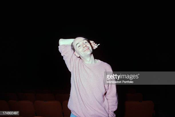 British choreographer mime and actor Lindsay Kemp smiling smoking a cigarette holding his arm behind his head 1980s