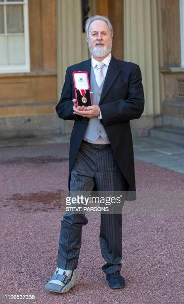 British choreographer Richard Alston poses with his medal after being appointed as a Knights Bachelor at an investiture ceremony at Buckingham Palace...