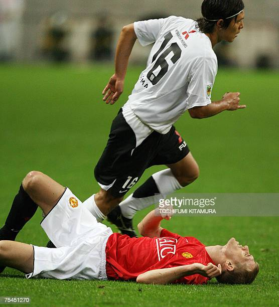 British club Manchester United forward Darren Fletcher falls on the pitch as Urawa Reds midfielder Takahito Soma runs beside him during their...