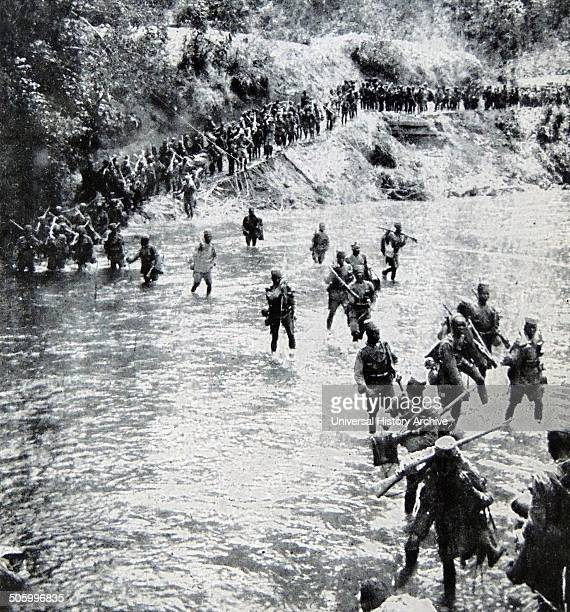 British colonial African soldiers cross a river in East Africa during World War One