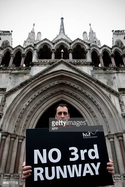 British comedian Alistair McGowan holds a placard outside the High Court in central London as he takes part in a protest against the government's...