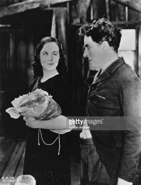 British comedian and director Charles Chaplin and actress Paulette Goddard to whom he was married for seven years star in the comedy 'Modern Times'...