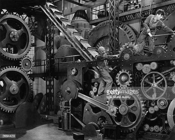 British comedian and director Charlie Chaplin in a scene from the silent comedy 'Modern Times' with Chester Conklin Chaplin also directed the film