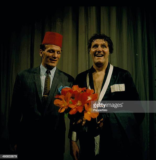 British comedian and magician Tommy Cooper right performs in a sketch with the boxer Henry Cooper on his television series 'Cooperama' in 1966