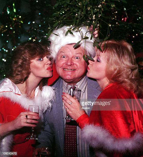 British Comedian and Writer Benny Hill Being kissed under the mistletoe by two of his 'Hill's Angels' Left LESLEY WOODS and Right SUE UPTON