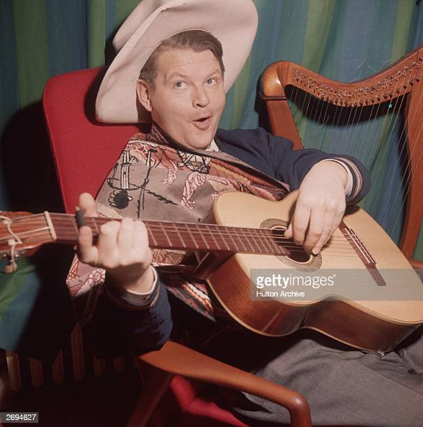 British comedian Benny Hill contrives to play the guitar in a lascivious manner