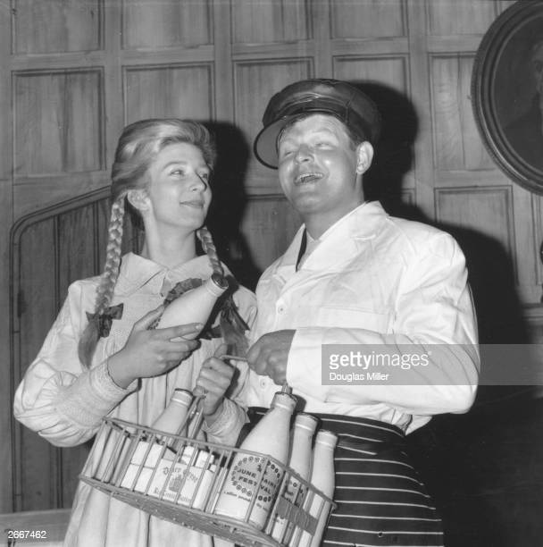 British comedian Benny Hill dressed as a milkman with a girl dressed as a 'cheese maiden' at a press party for a dairy festival