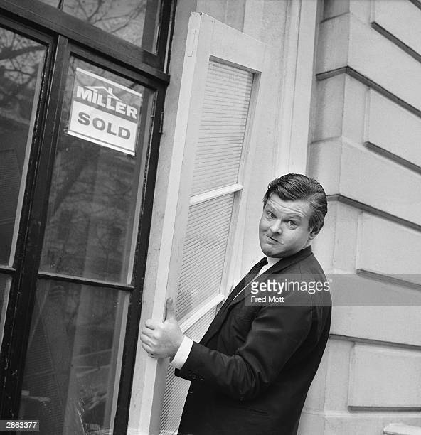 British comedian Benny Hill moving a glass door during renovations to his flat in Kensington London