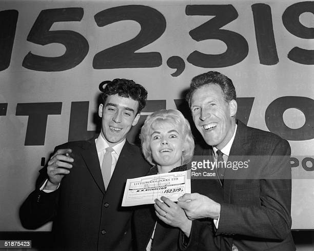 British comedian Bruce Forsyth presents a cheque for £152319 to Yorkshire miner Keith Howard Nicholson and his wife Vivian winners of the Littlewoods...