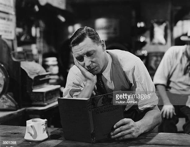 British comedian George Formby buries himself in a book in the Columbia comedy 'George In Civvy Street' directed by Marcel Varnel