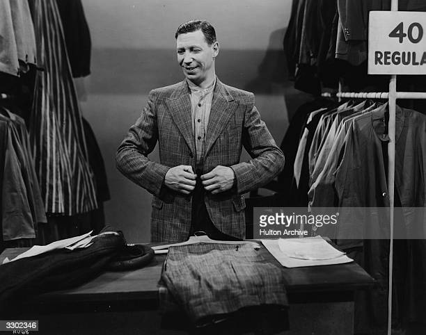 British comedian George Formby tries on a new suit in the Columbia film 'George In Civvy Street' a mild comedy directed by Marcel Varnel