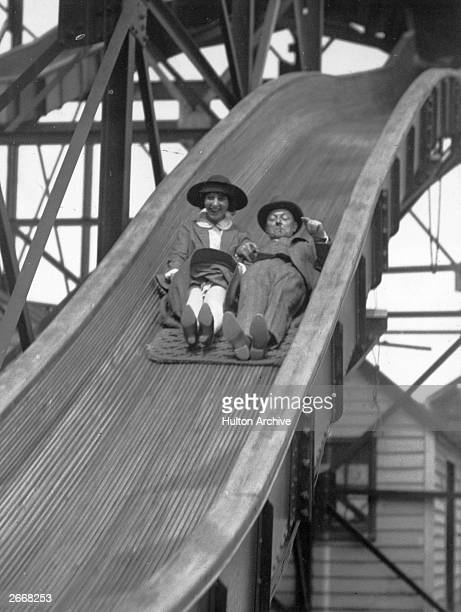 British comedian George Graves and his wife, actress Flora Courtenay, enjoying themselves as they slide down the 'Jack and Jill' in the amusement...