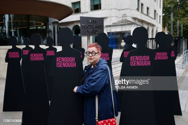 British comedian Jo Brand poses with cut-out silhouettes representing women outside the Metropolitan Police headquarters New Scotland Yard in London...