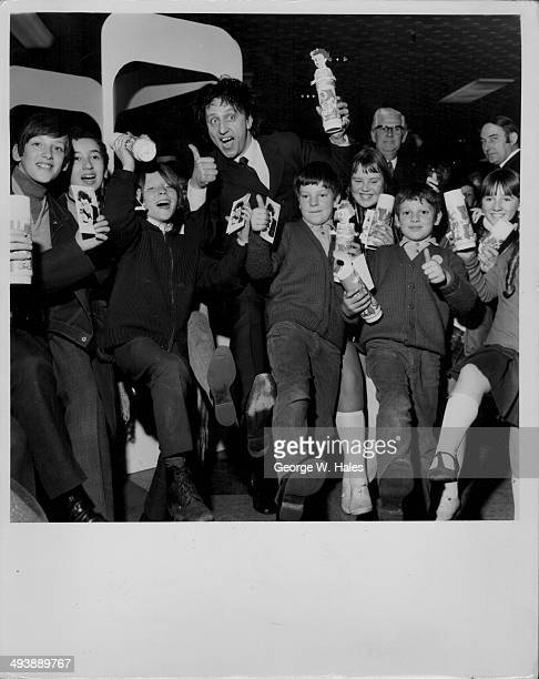 British comedian Ken Dodd posing with a group of children to advertise his new Diddy Vacuum Flask London March 25th 1970