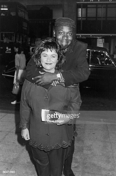 British comedian Lenny Henry puts his arms around his wife comedienne Dawn French who is holding a programme for 'Lenny Live and Unleashed' July 1989