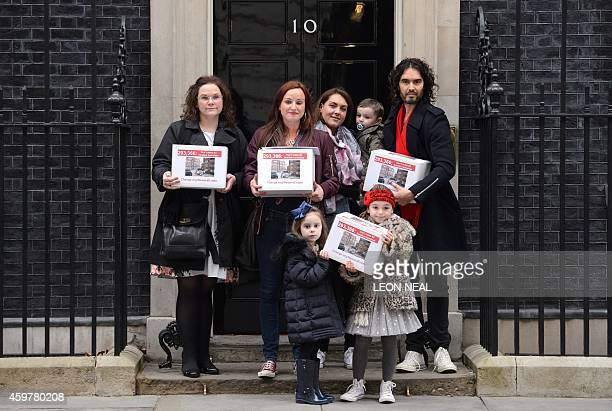 British comedian Russell Brand poses on the doorstep of Downing Street in central London on December 1 with New Era housing estate tenants Lynsay...