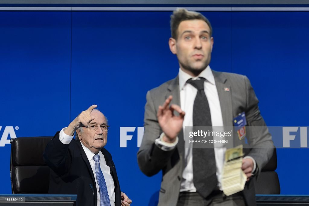 British comedian Simon Brodkin (C) gestures in front of FIFA president Sepp Blatter (L) during a press conference at the football's world body headquarter's on July 20, 2015 in Zurich. FIFA said today that a special election will be held on February 26 to replace president Sepp Blatter.