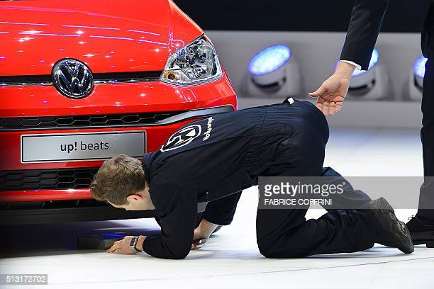 British comedian Simon Brodkin inspects under a new model at German carmaker Volkwagen stand as he disrupts a presentation a the press day of the...