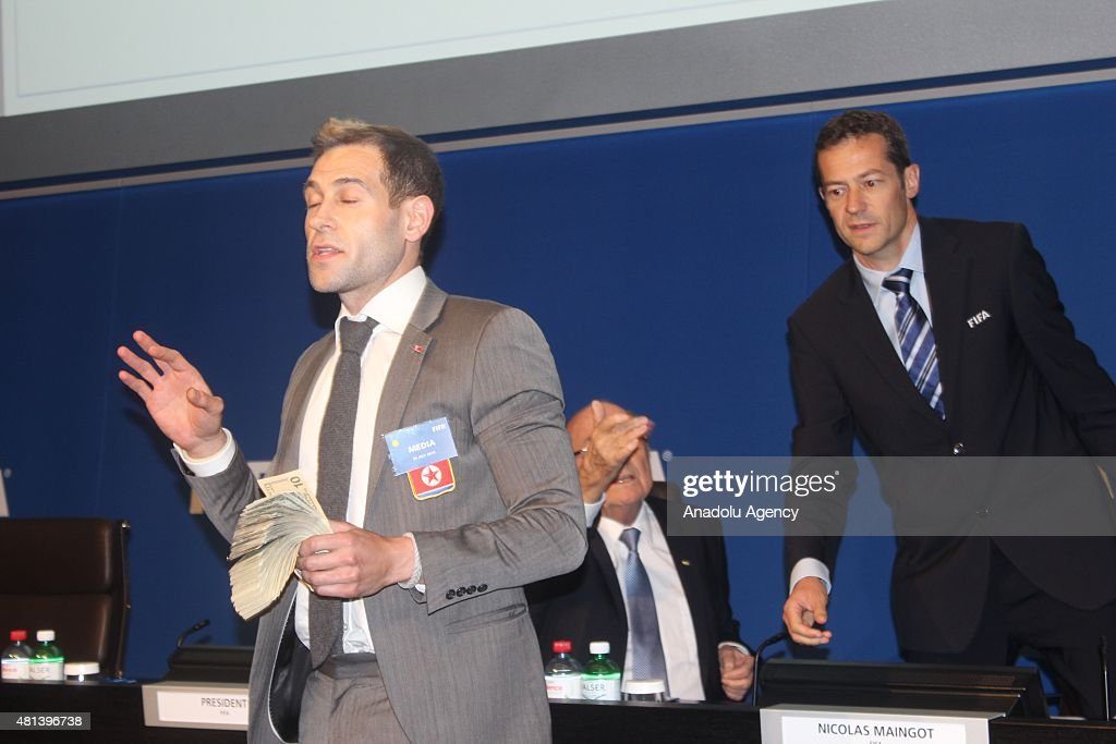 British comedian Simon Brodkin throws money at FIFA President to protest while Sepp Blatter is making a press conference following a meeting about the date for its next presidential election on Monday, in Zurich, Switzerland, on July 20, 2015.