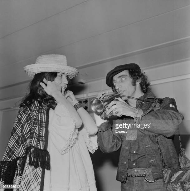 British comedy writer and actor Marty Feldman playing a trumpet while his wife Lauretta Sullivan cover her ears UK 26th November 1971